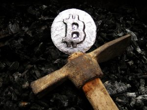 Silver bitcoin coin and pickaxe.