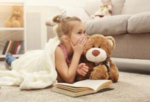 Girl whispering secrets to her teddy bear.