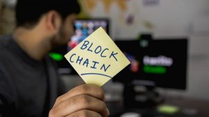 Man working on his computer while holding a sticky note labeled block chain.