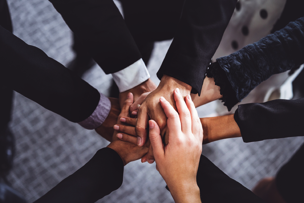 Group of people forming a circle with hands in the middle.