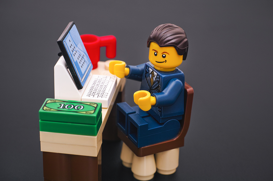 Lego man sitting at a desk.
